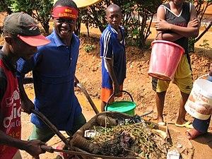 Children cart dirt and debris away during a co...