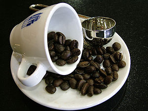 A fallen coffee cup with beans pouring out.