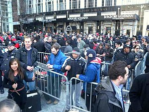 English: Looking south at crowds waiting in ma...