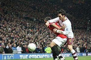 Arsenal's Cesc Fàbregas (white shirt) duels wi...