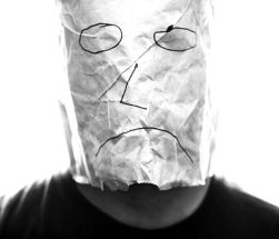 File:Gray paper bag with sad smiley over head.jpg