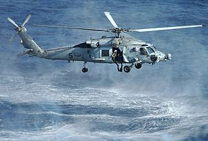 An HH-60H deploying a SAR swimmer