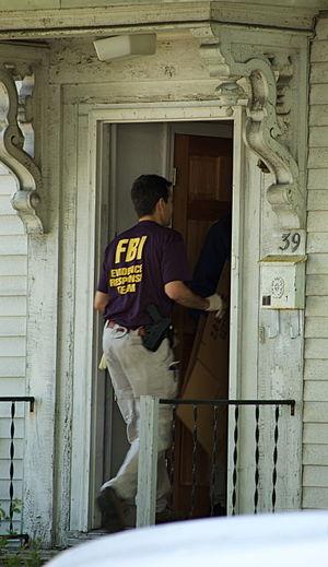 An FBI Evidence Response Team agent enters 39 ...