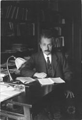 Einstein, sitting at a table, looks up from the papers he is reading and into the camera.