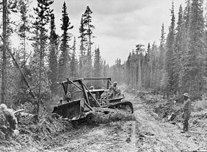 Caterpillar tractor with grader widening the r...