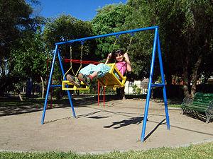 English: A girl on a swing. Español: Una niña ...