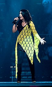 Sunidhi Chauhan performing on stage wearing a black and yellow dress