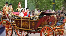 Couple sitting in a decorated horse-drawn open-top carriage, with two well-dressed guards sitting behind the newly-weds. The carriage is flanked on the far side by excited well-wishers