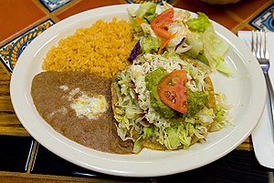 A beef tostada on a plate with refried beans, ...