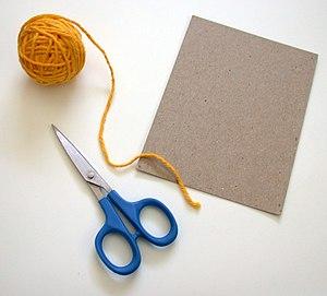 Supplies for making a yarn doll: yarn, scissor...