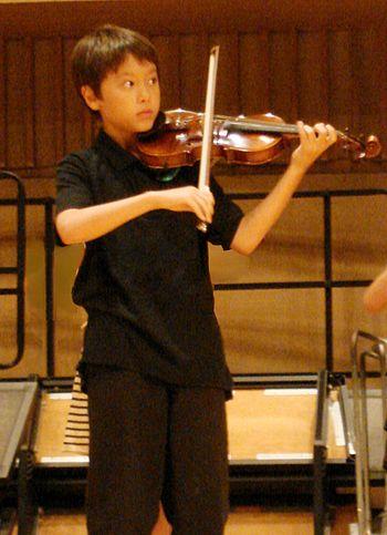 English: Asian american boy playing violin