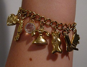 A gold charm bracelet worn on the arm. Visible...