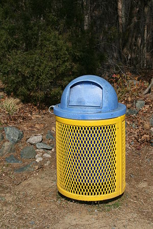 A yellow metal trash can with a blue plastic l...