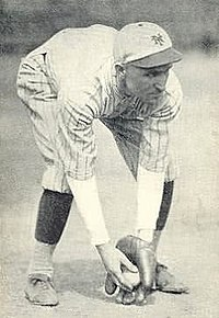 A black and white photograph of a man in a baseball uniform bending over to field a baseball.
