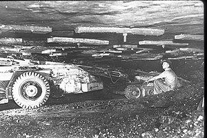 Miners work in a mine with a low roof
