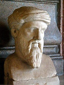 Marble bust of a man with a long, pointed beard, wearing a tainia, a kind of ancient Greek headcovering in this case resembling a turban. The face is somewhat gaunt and has prominent, but thin, eyebrows, which seem halfway fixed into a scowl. The ends of his mustache are long a trail halfway down the length of his beard to about where the bottom of his chin would be if we could see it. None of the hair on his head is visible, since it is completely covered by the tainia.