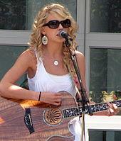 Taylor Swift, Draagt Een witte jurk en Een zonnebril, Speelt Een Akoestische gitaar, while sterven zich hier Een microfoonstandaard