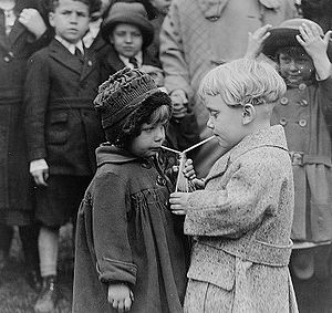 A boy and a girl sharing a drink, each with th...