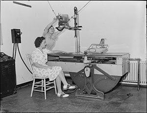 R.N., Hazel Jamison, adjusts the X-Ray machine...