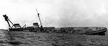 A large warship rolls onto its side