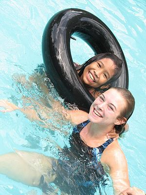 Two young girls having fun in swimming lessons.
