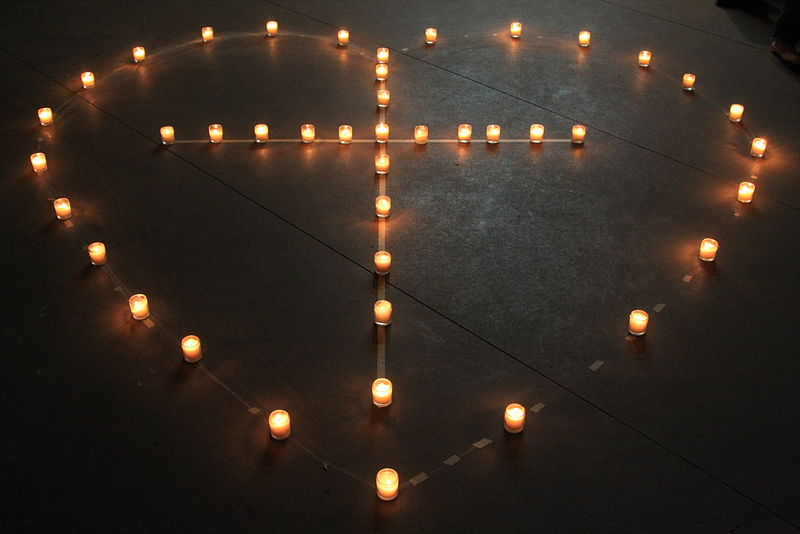 A cross in a heart, made from candles