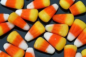 Candy corn strewn on a black background.