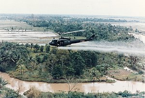 English: U.S. Huey helicopter spraying Agent O...
