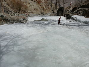 English: A monk ice skating on a frozen river.