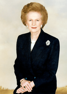 A professional photograph of a lady with ginger-blonde hair, sitting in a traditional style and wearing jewellery.