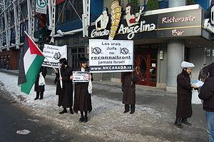 English: Neturei Karta hand out anti-Israel fl...
