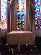 A large pink/cream-colored box in front of a stained glass window.