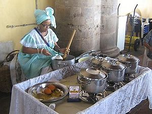 woman cooking traditional dishes in a street k...