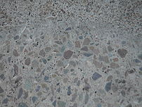 Grinding concrete exposes aggregate stones.