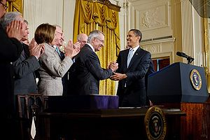 President Barack Obama shakes hands with Senat...