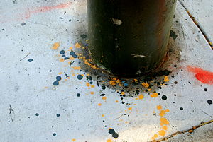 Black painted pole in concrete with multicolor...