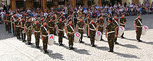 Uniformed band members standing in formation, the band leader in front.