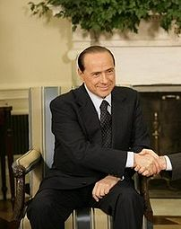 Silvio Berlusconi shaking hands with George W....