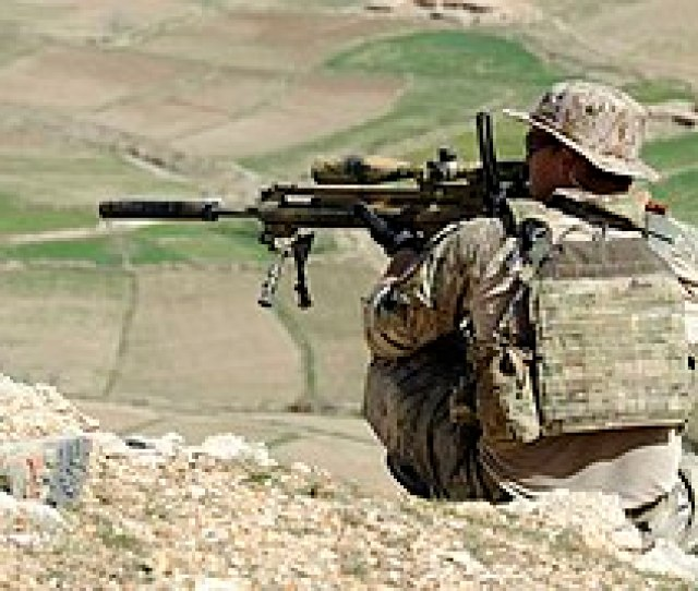 A Coalition Special Operations Forces Member Fires His Sniper Rifle From A Hilltop During A Firefight
