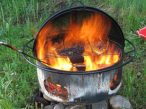 English: A burning barbecue used in a summer c...