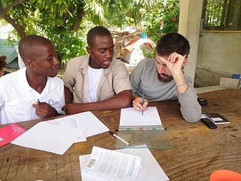 A French-speaking Canadian volunteer helps two...