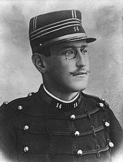 Head and torso of a young man wearing military uniform with spectacles and a moustache