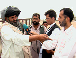 A reporter for RFE/RL's Afghan Service interviews a citizen in Helmand, Afghanistan