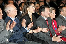Abdullah, Rania and two other people applauding in an audience