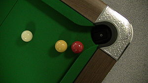 A British standard pool table, showing a cue b...