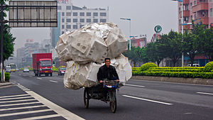 English: A man is riding his overloaded tricyc...