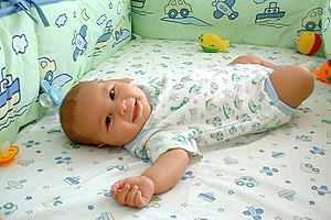 A smiling baby lying in a soft crib.