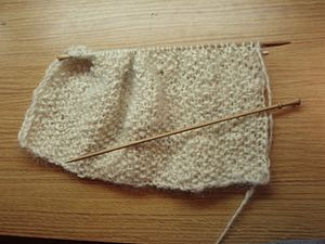 A picture of a scarf being knitted on single p...