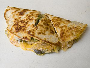 A quesadilla, a tortilla folded over shredded ...