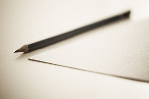 a sharpened blue-grey pencil lies on a table n...